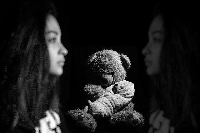 Jeune femme et ours en peluche représentant les blessures de l'âme durant l'enfance.