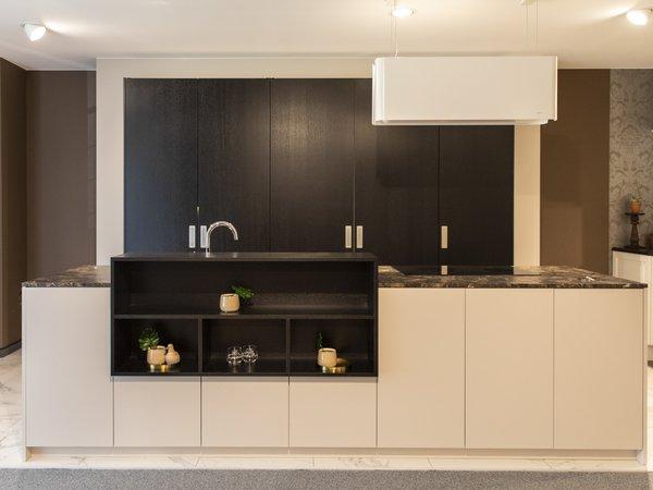 zwarte keuken met kookeiland en witte kasten