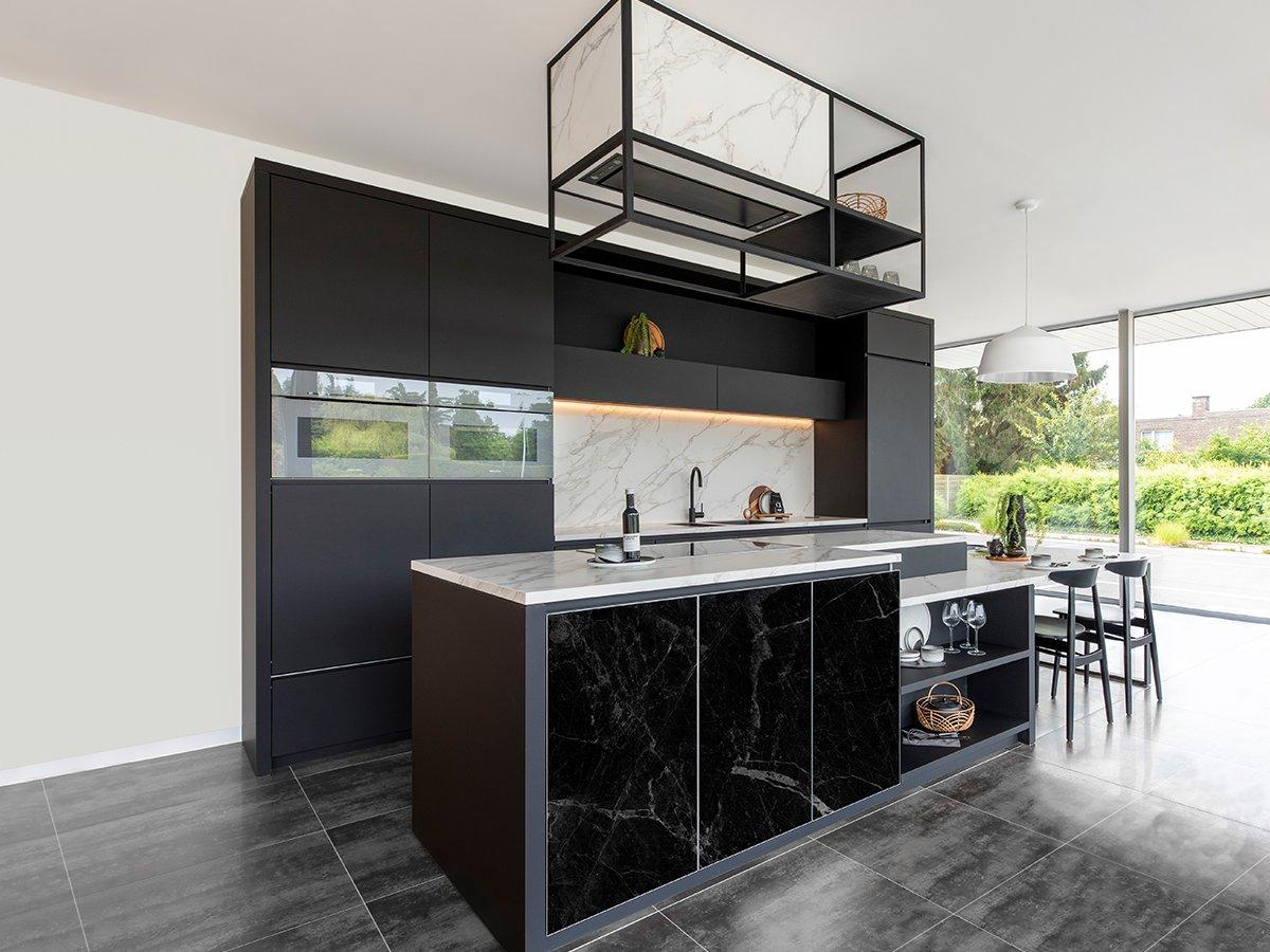 Keuken met eiland in zwart laminaat met geprinte glasdeuren met marmer motief