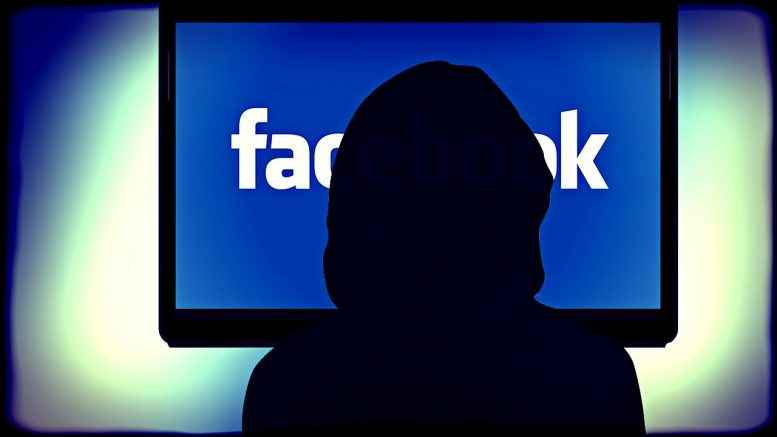 Shadow in front of facebook on computer screen.