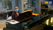 Guest Services Specialist Emily Wheeler played piano in the main lobby of Mott Children's Hospital on the tense afternoon of Jan 6