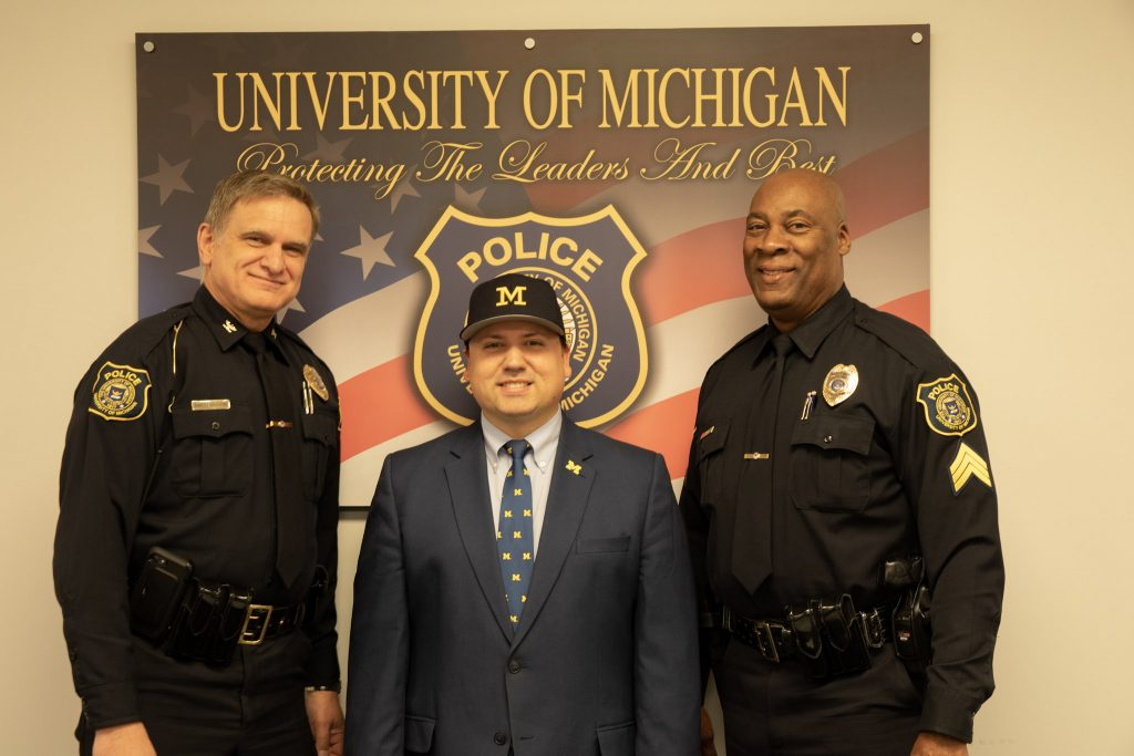 U-M Police Chief Robert Neumann, advocate Xavier DeGroat and Sgt. Gary Hicks pose for a photo at the U-M Police Department in January 2020.