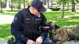 Officer Joseph Dunny and K-9 Tank sit together on the Diag