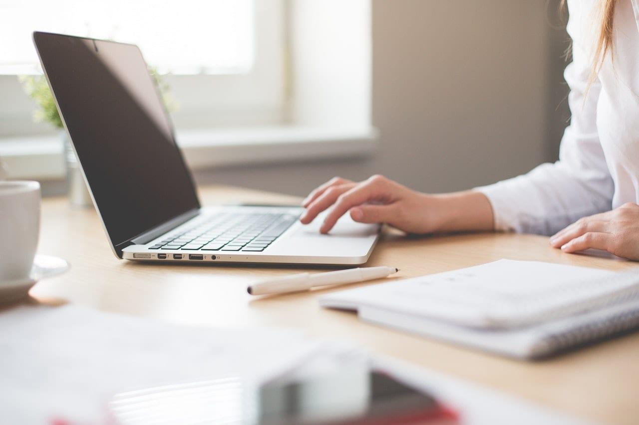 Como montar um portfolio sem ter clientes. Imagem mostrando uma pessoa trabalhando com um notebook que está em cima da mesa.