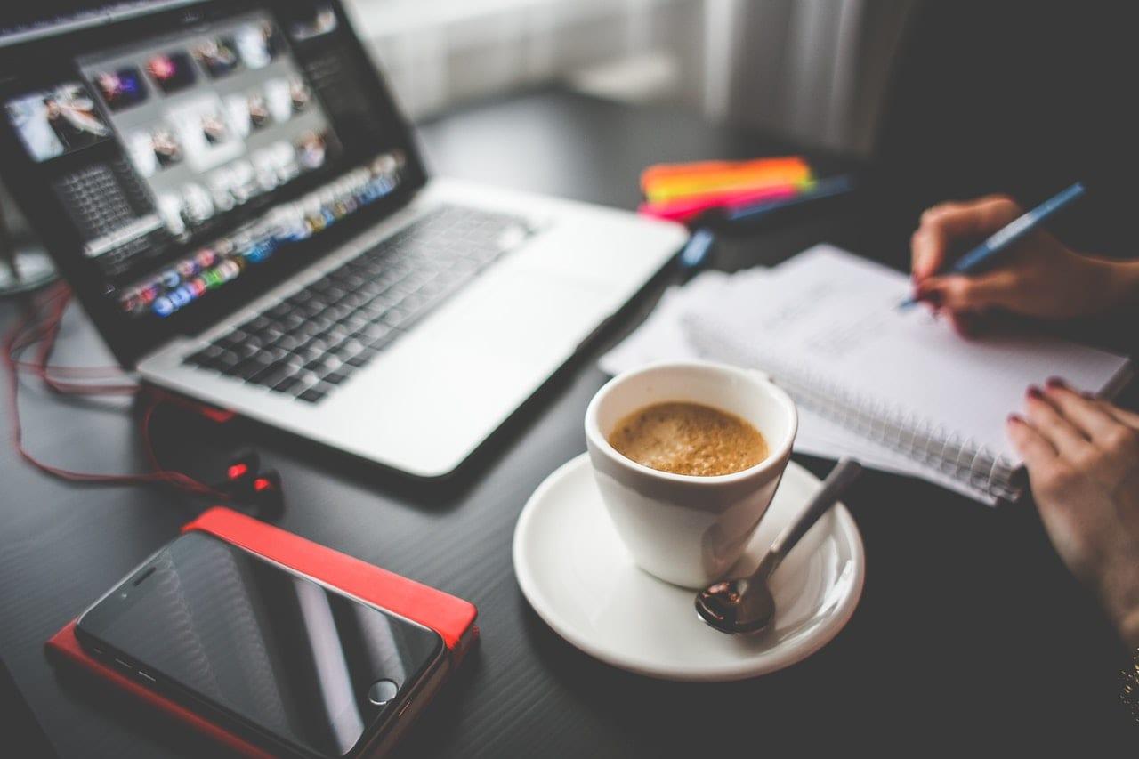 Portfolio: imagem de alguém trabalhando em uma mesa com laptop, celular, caderno e um cafezinho.