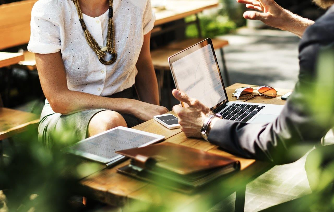 5 diferenças entre portfolios eficientes e portfolios ruins: duas pessoas sentadas, conversando ao redor de uma mesa com notebook e cadernos em cima.