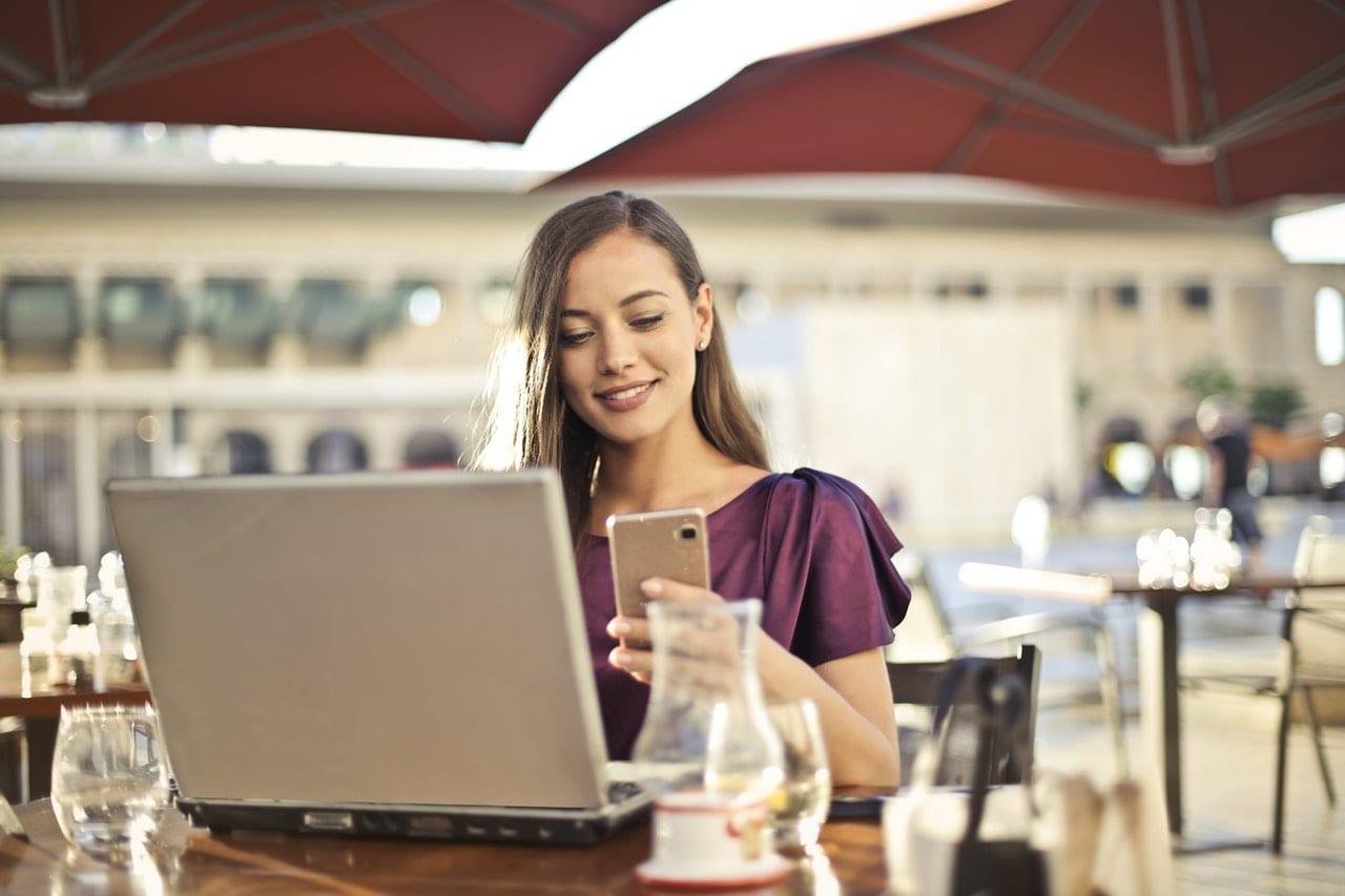 5 diferenças entre portfolios eficientes e portfolios ruins: mulher vestindo roxo sentada na cadeira enquanto segura telefone.