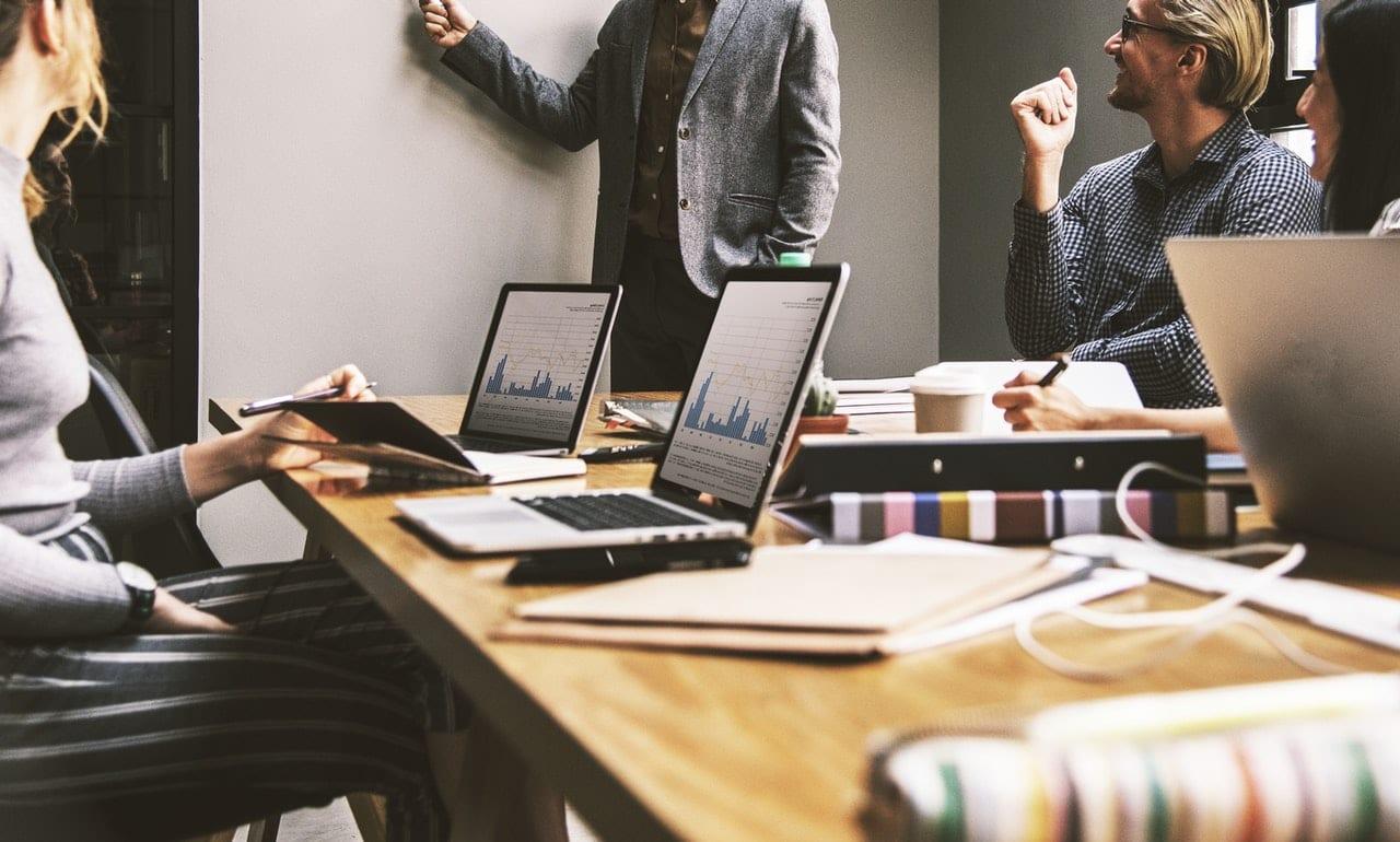 A evolução do portfolio: foto mostrando profissionais em reunião. Parecem estar otimistas.