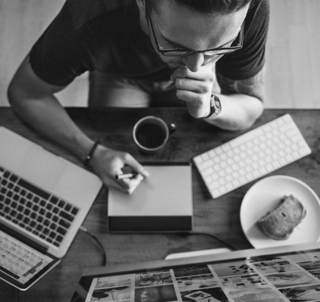 Homem trabalhando com vários eletrônicos em cima da mesa, pensando sobre o que colocar em seu portfolio.
