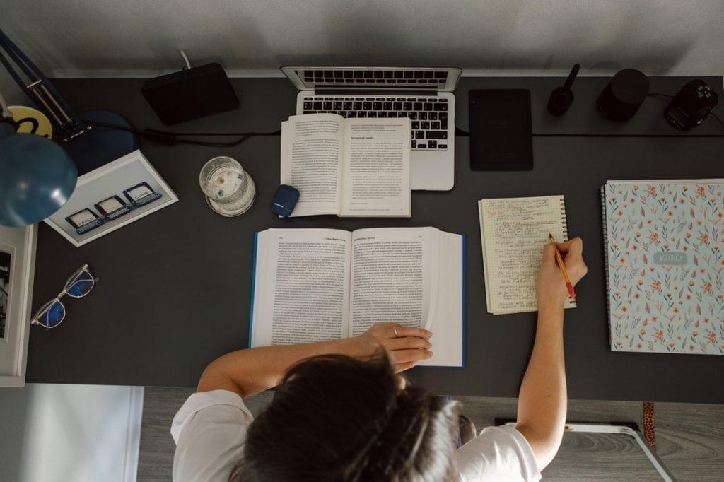 12 informações relevantes para o seu portfolio: mulher trabalhando em mesa com diversos livros, caderno e notebook.