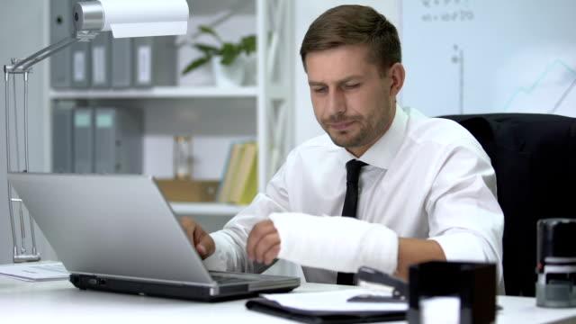 Homem com braço quebrado mexendo no computador. ARIA com certeza pode ajudar neste tipo de situação.