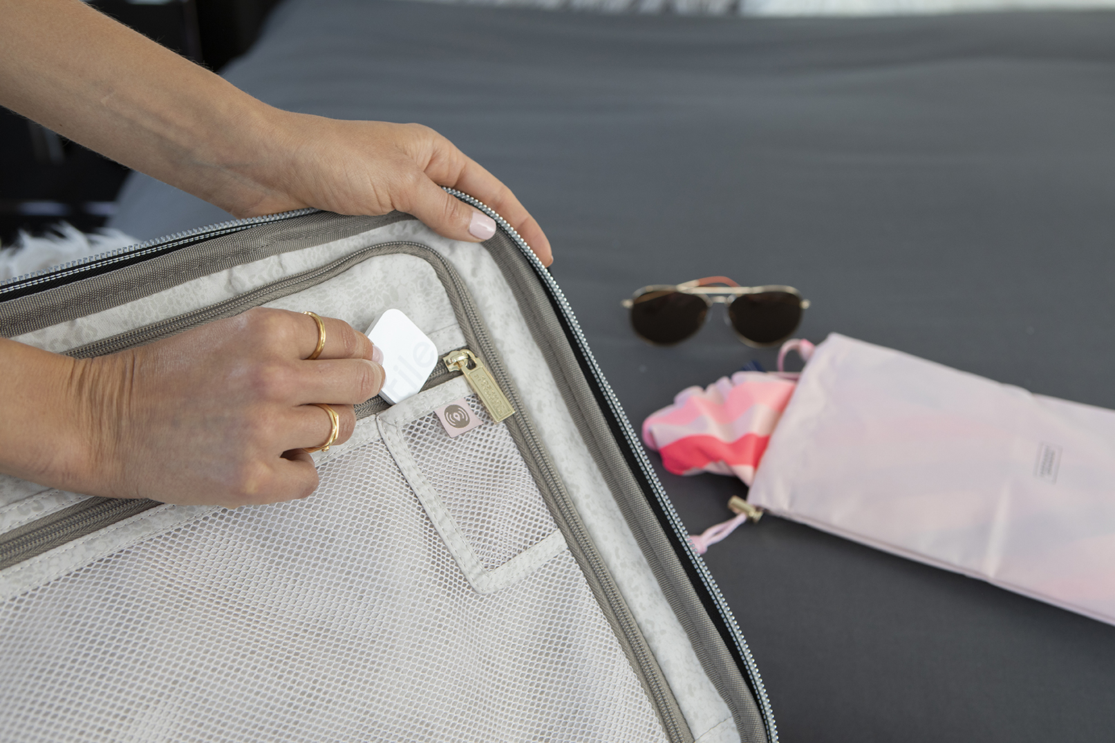 Woman placing a Tile bluetooth tracker inside pocket