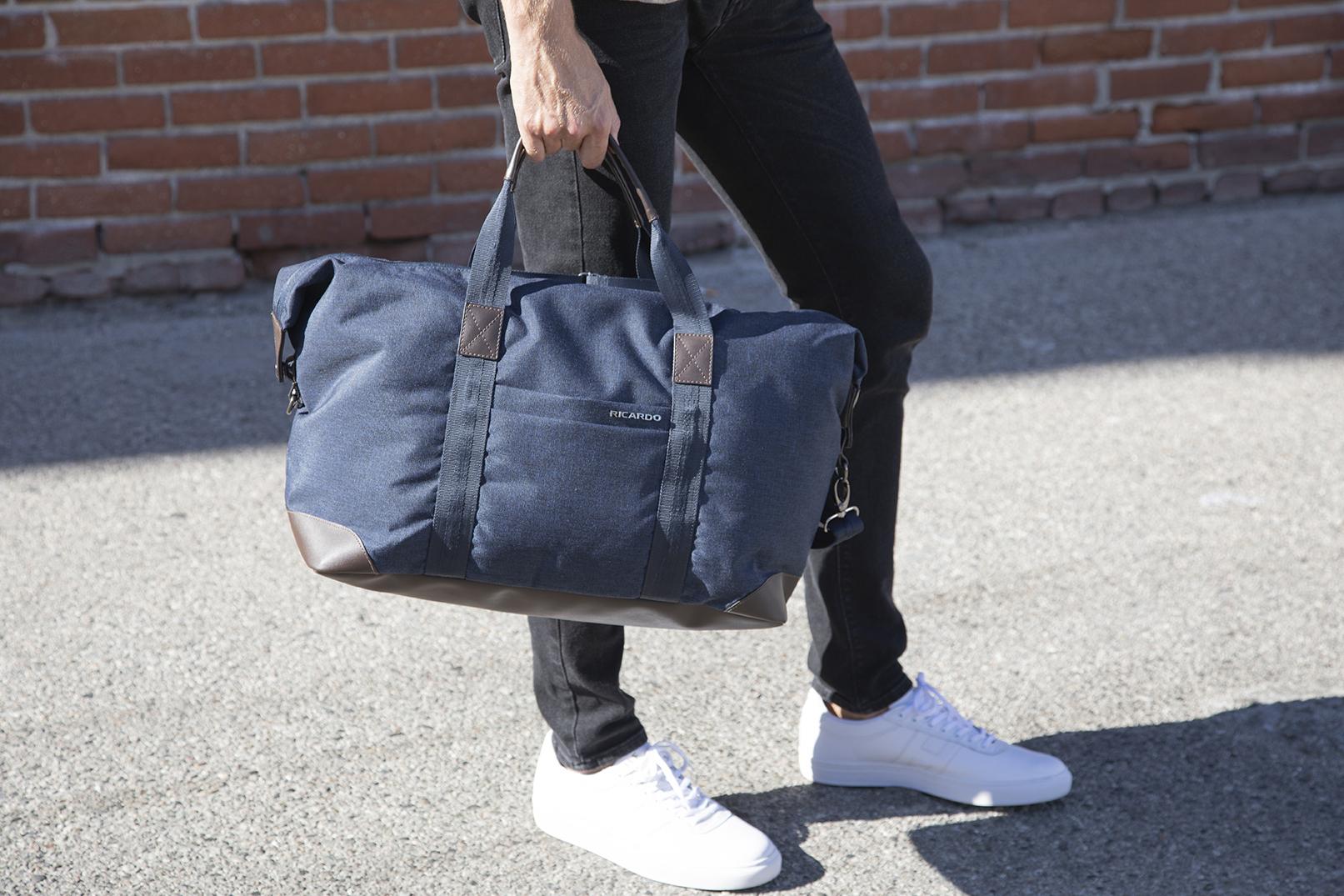 Men holding a duffel.