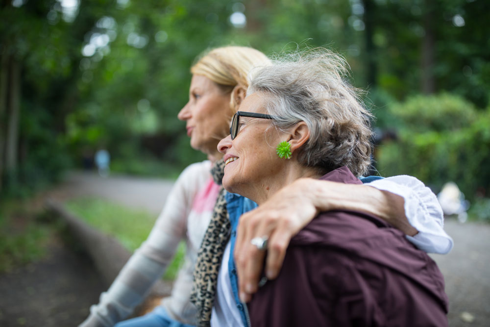 A woman puts her arm around her senior mother's shoulders as they sit outside on a park bench