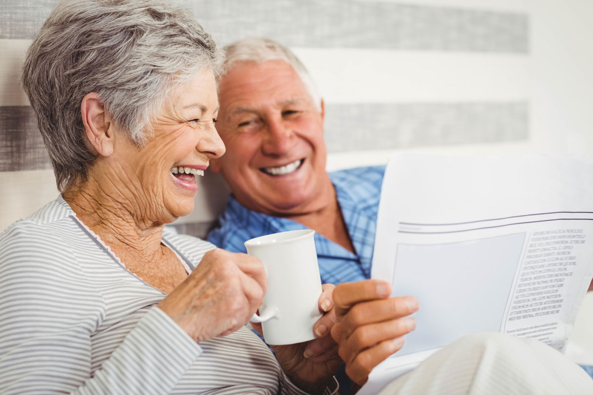 a senior couple laughing and enjoying cups of coffee