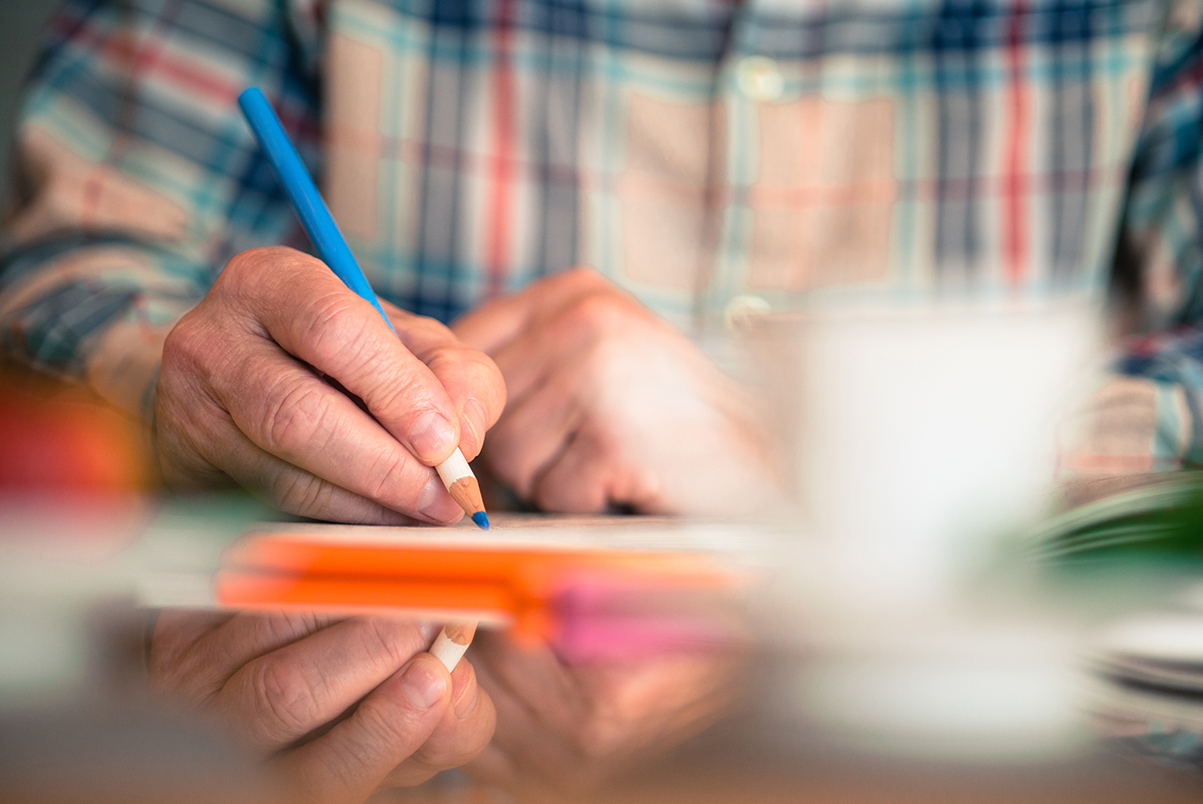 An elderly person uses a pencil to write a note on a post-it