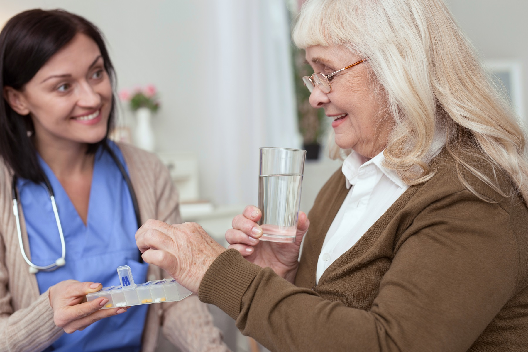 Senior woman receiving a little help with medication from a nurse