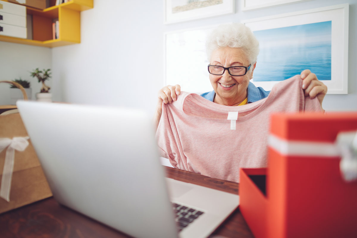 A senior woman opens a present while on a video call with family