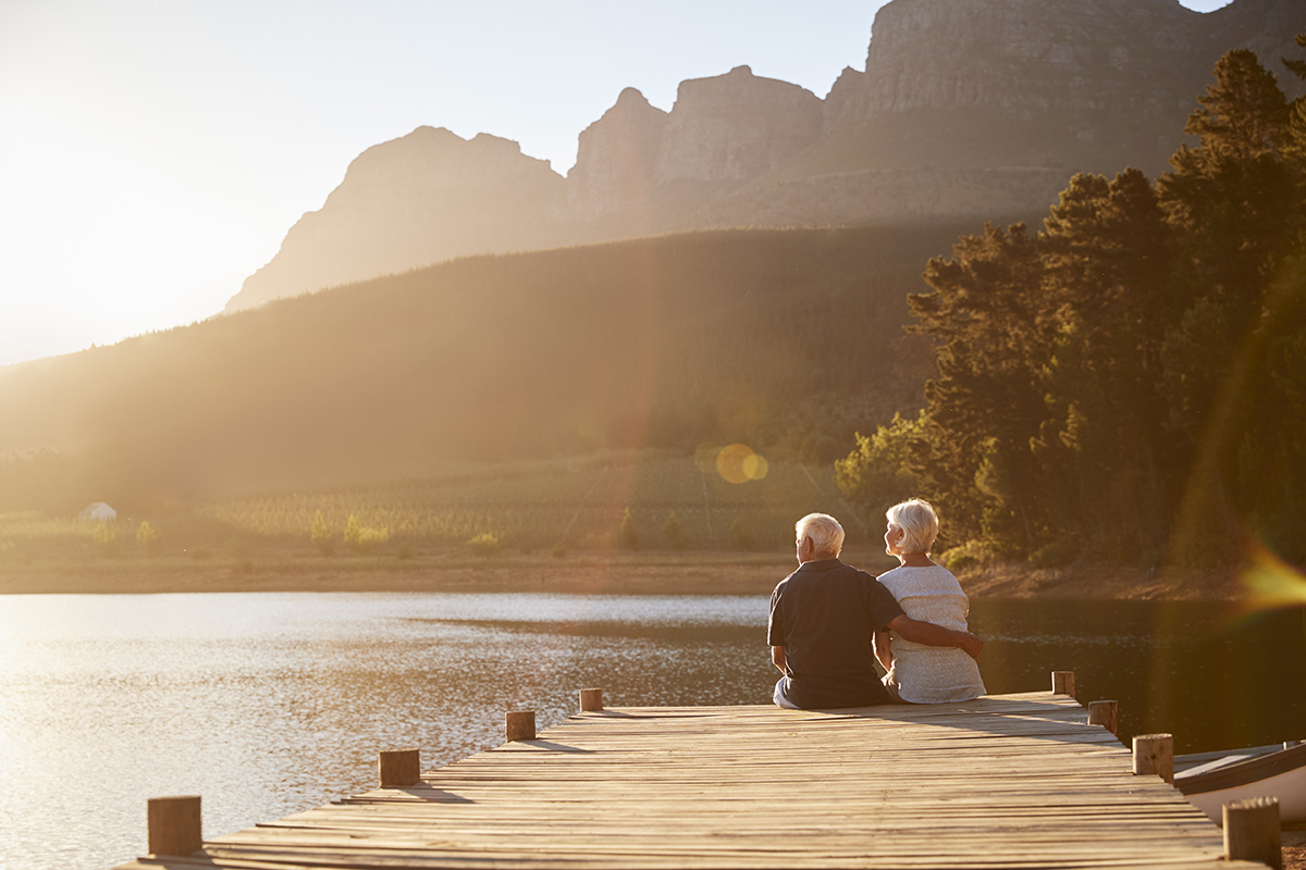 a senior couple sitting on a wooden dock overlooking a lake