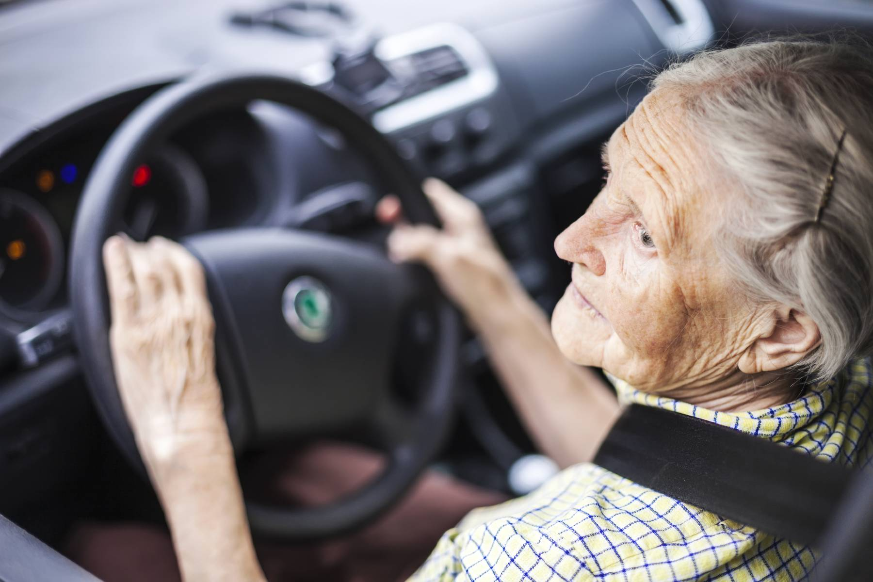 elderly woman sitting in the driver's seat of a car