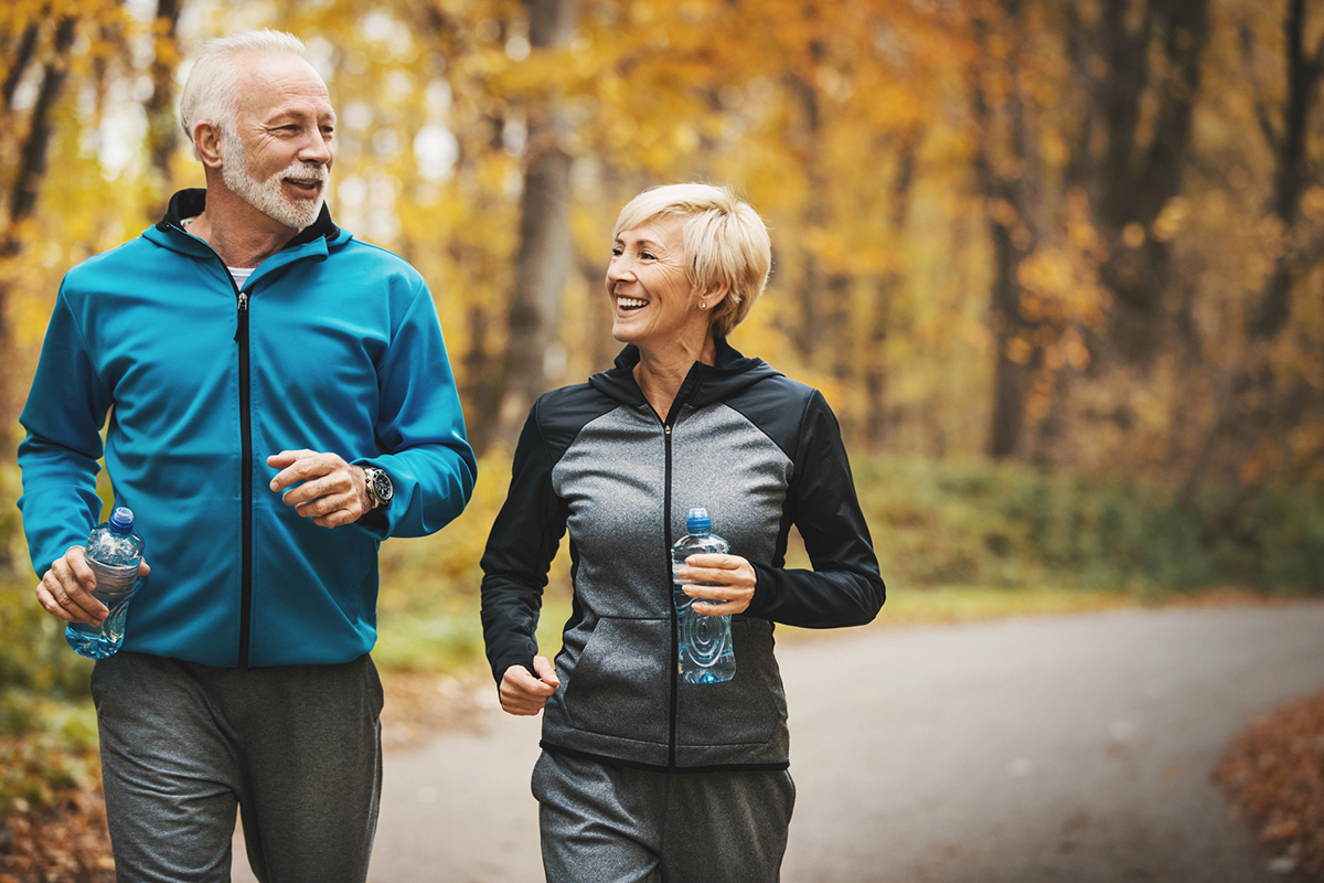 a senior couple going for a jog on a trail in a forest