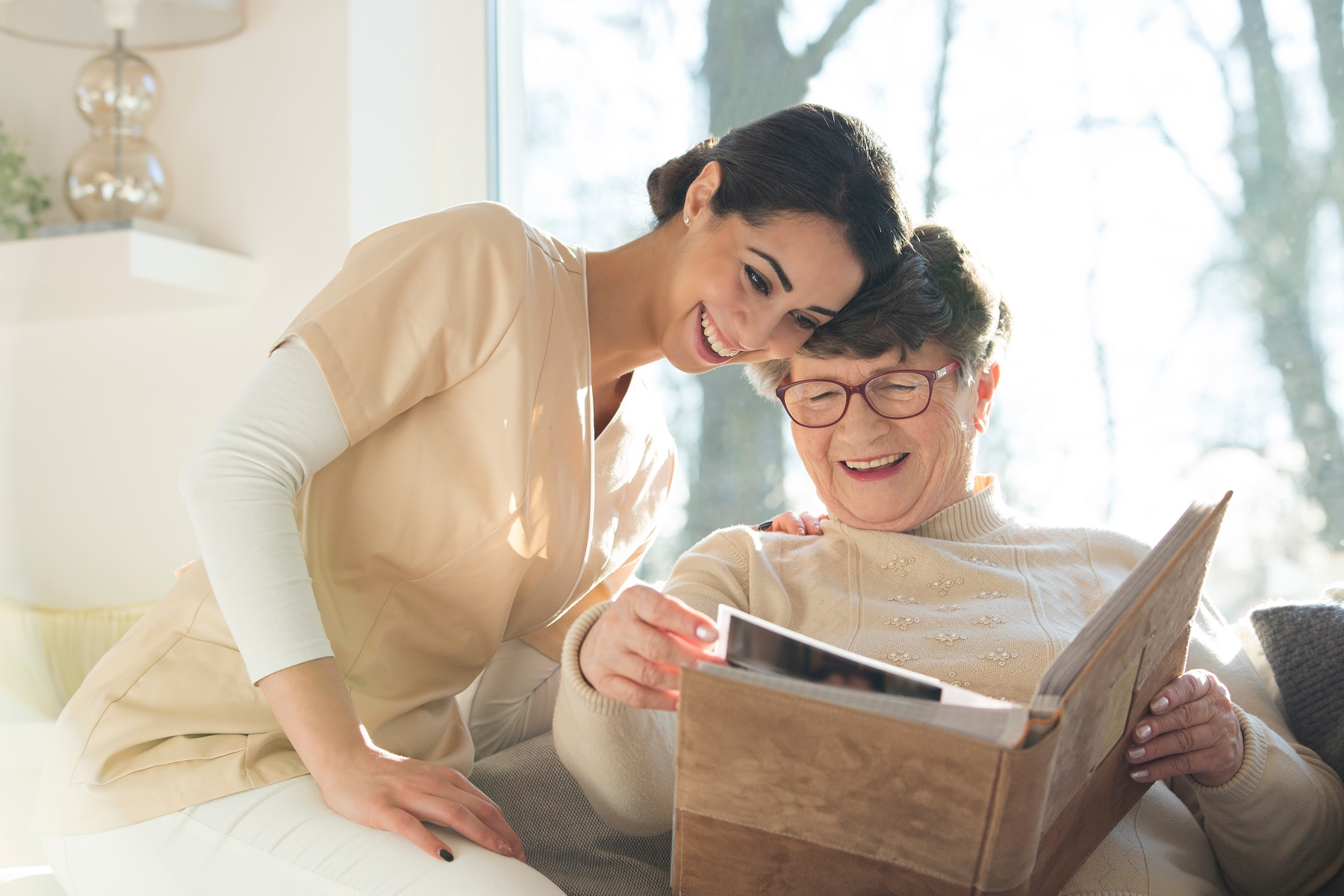 Memory care team member and senior resident looking at photo album