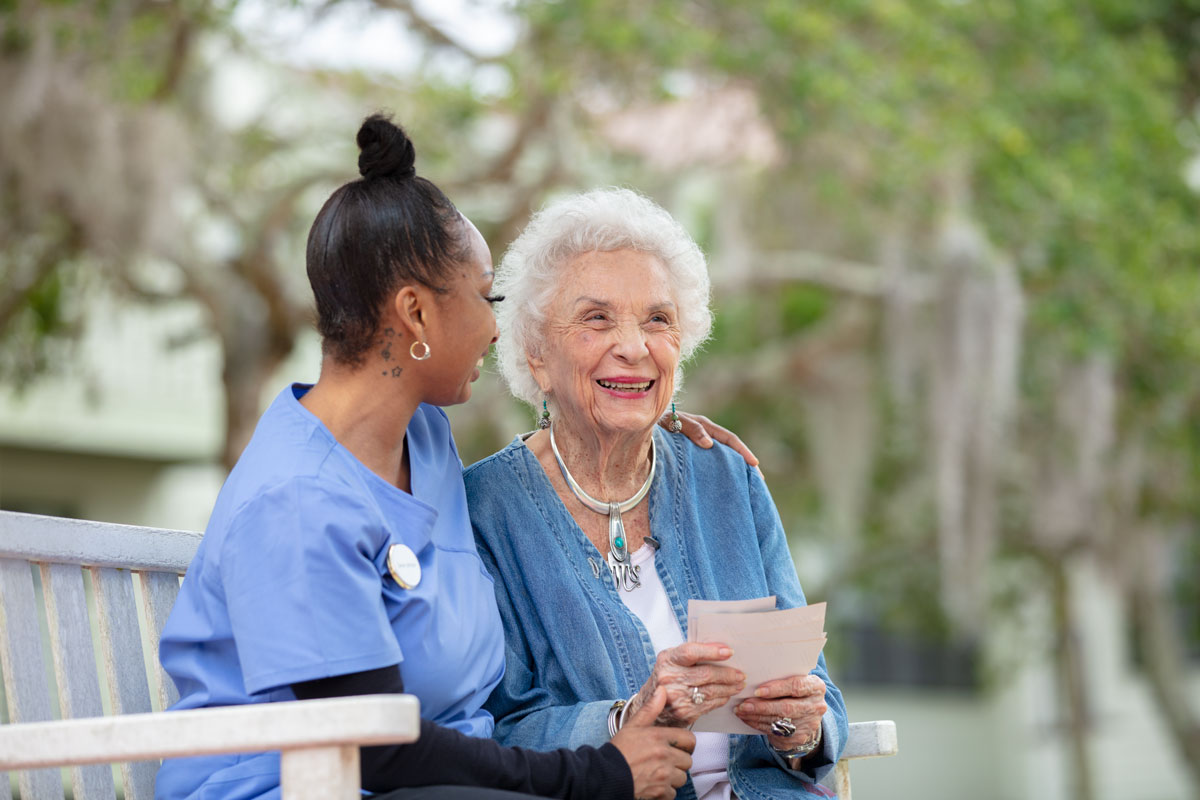 A health care professional sits outside on a bench with an elderly woman