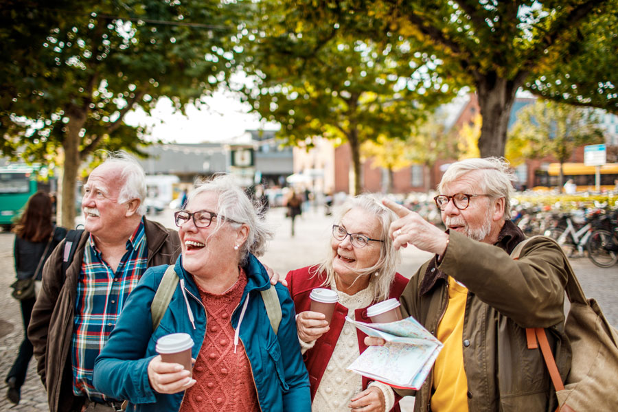 A group of seniors together outdoors, walking the town and drinking coffee