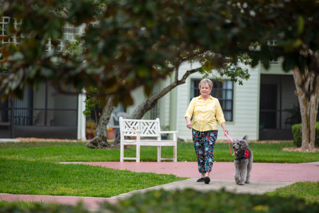 Senior woman walking her dog at a senior living community