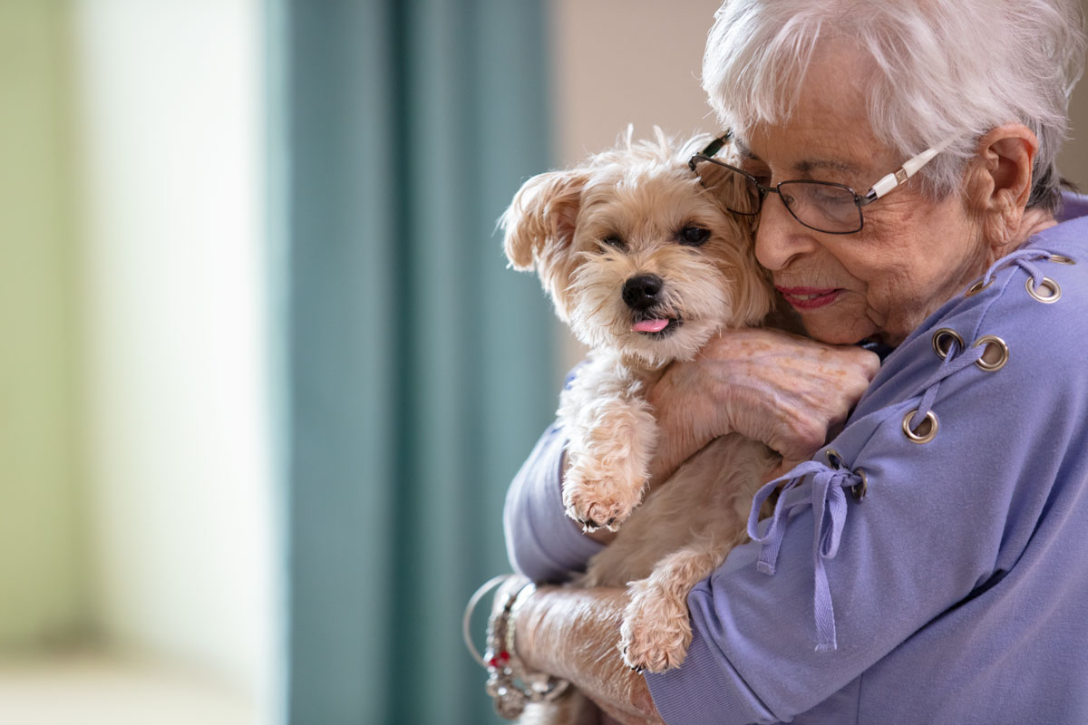 Senior woman hugging her small dog