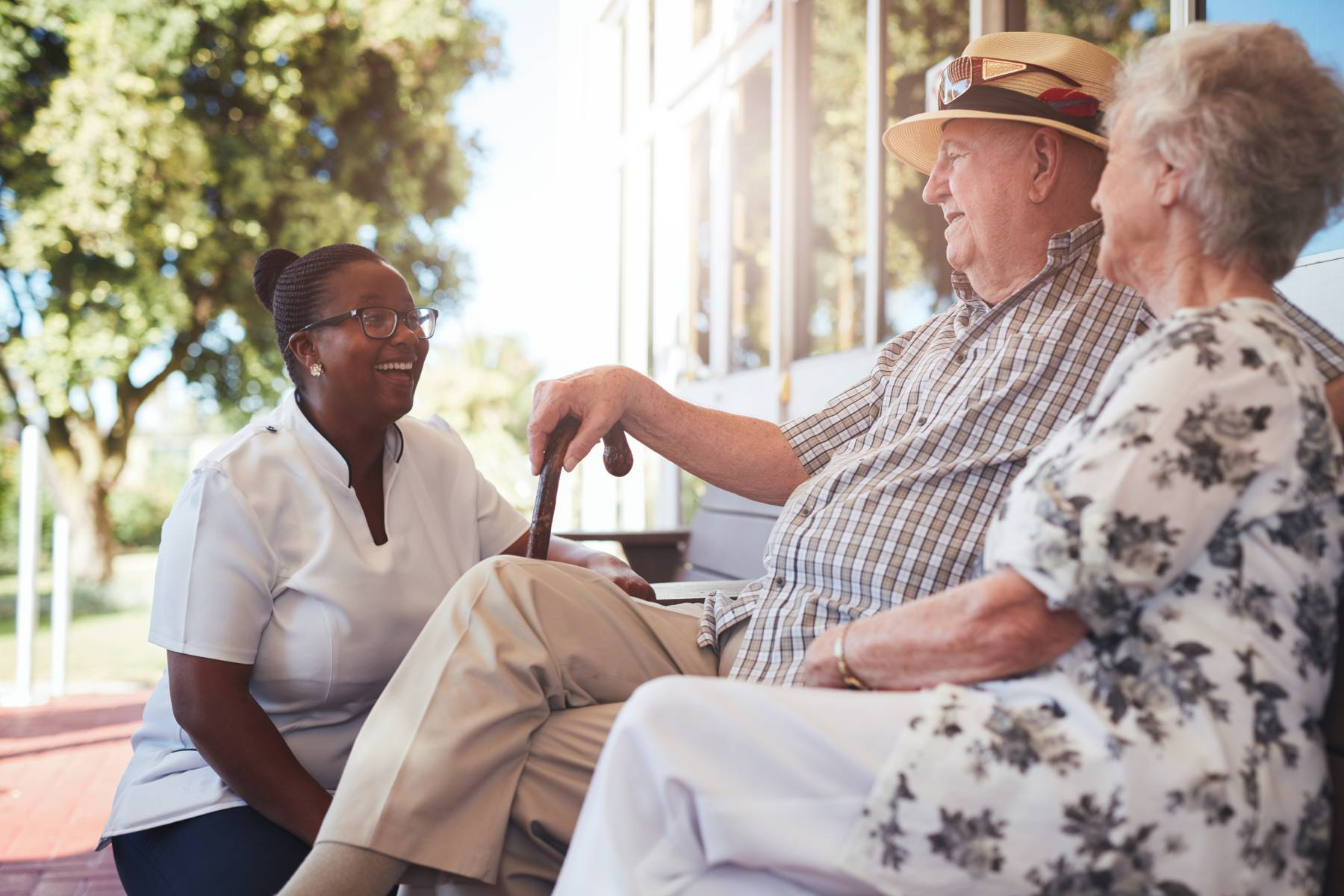 senior couple in assisted living talking to a caregiver