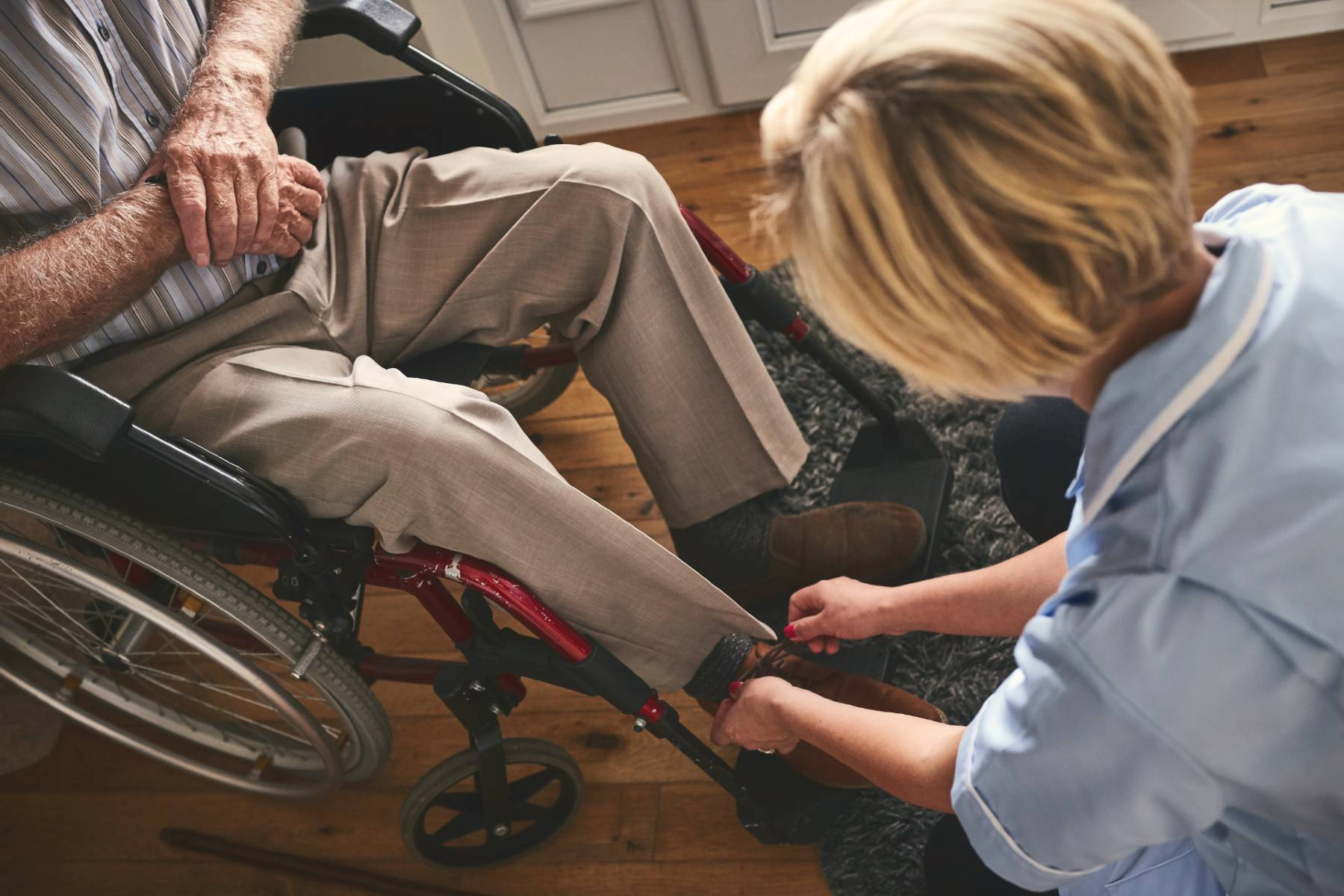 A women bends over to tie the shoe of a senior man in a wheel chair