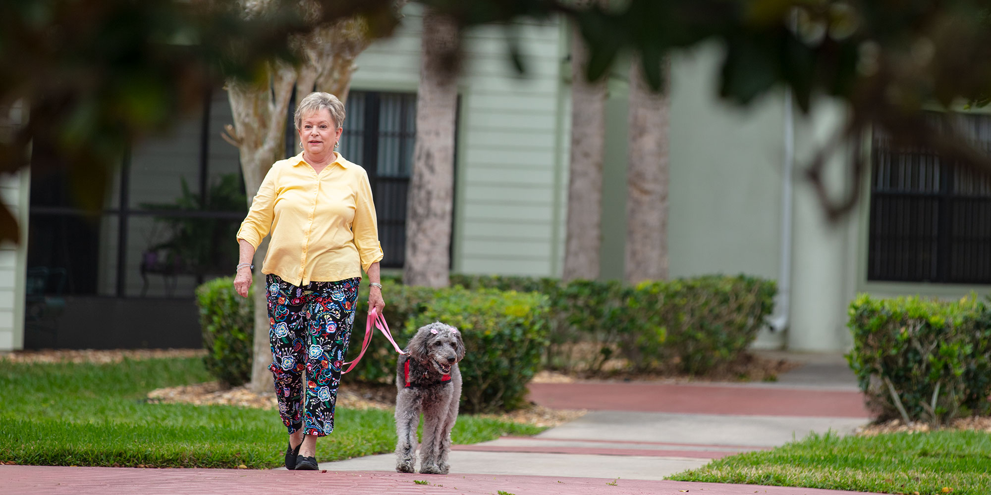 Elderly woman walking her dog at a senior living community