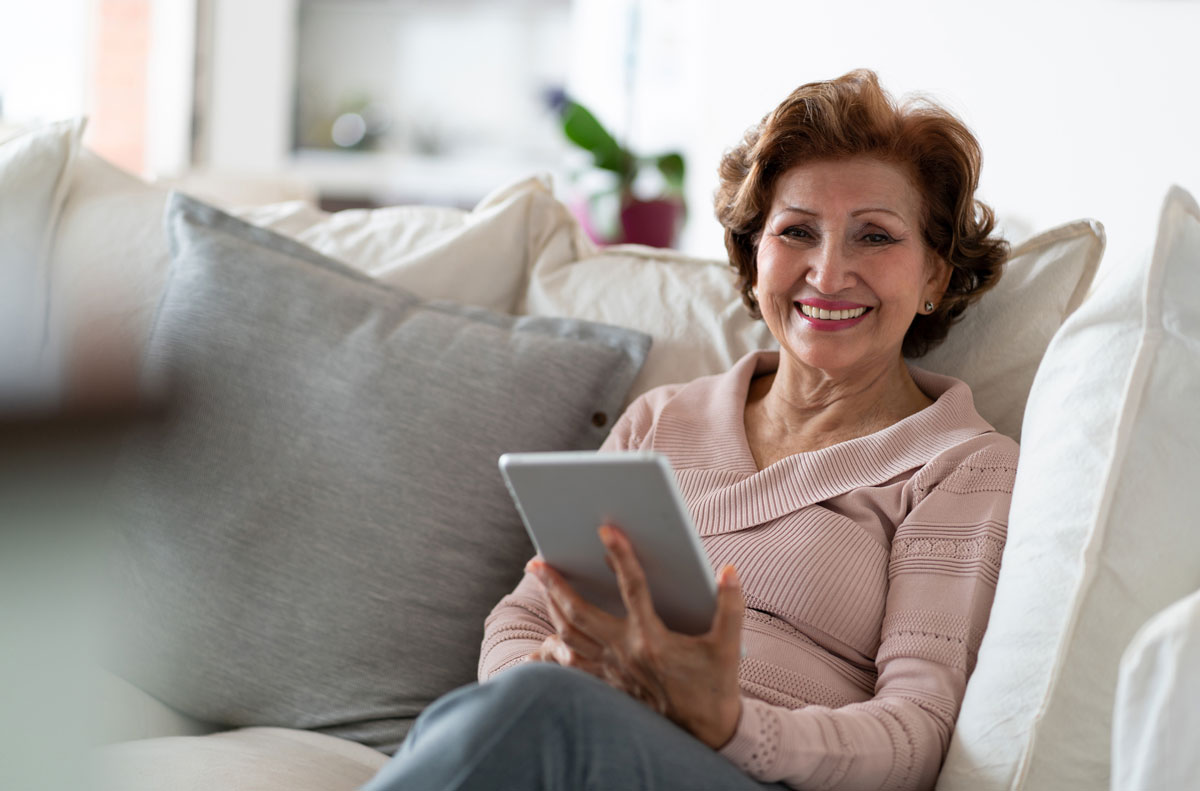 senior woman smiles at the camera while sitting on a couch looking at a tablet