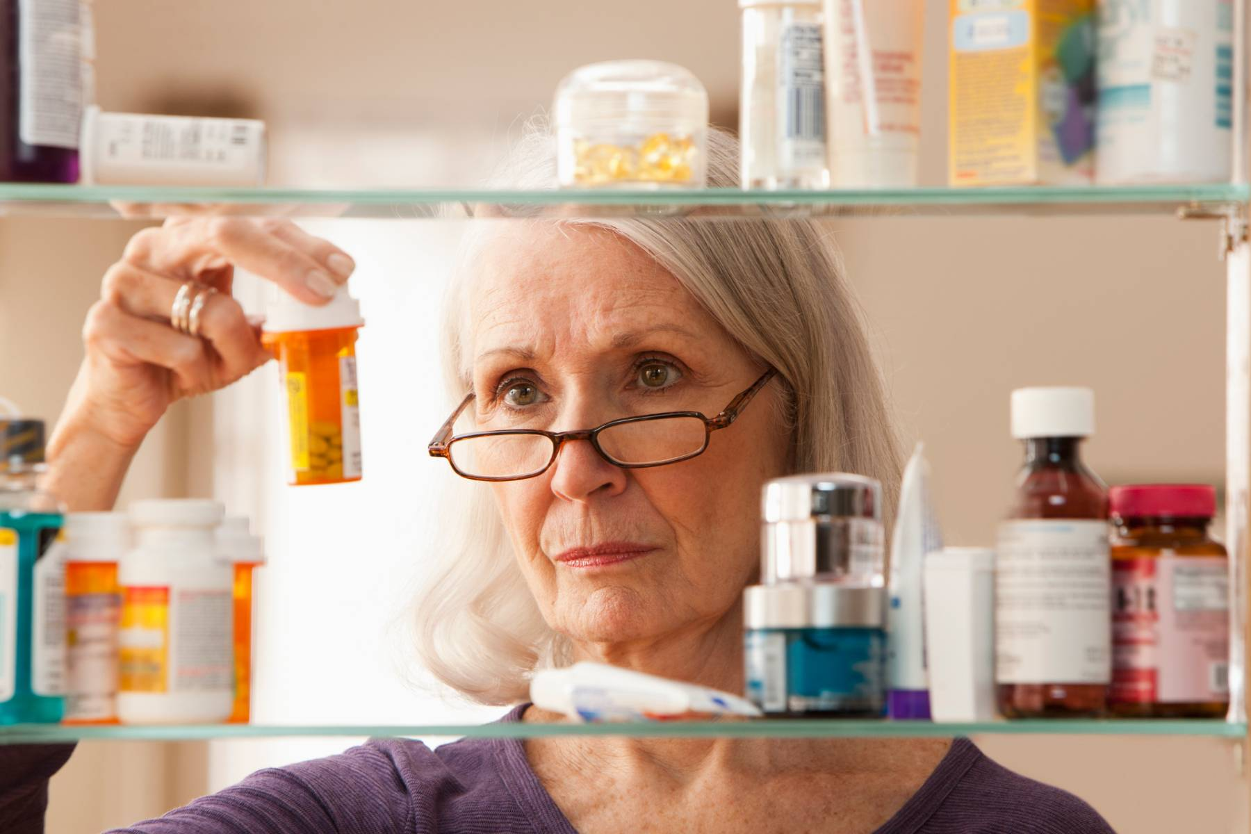 A senior woman peers at medicine in her medicine cabinet