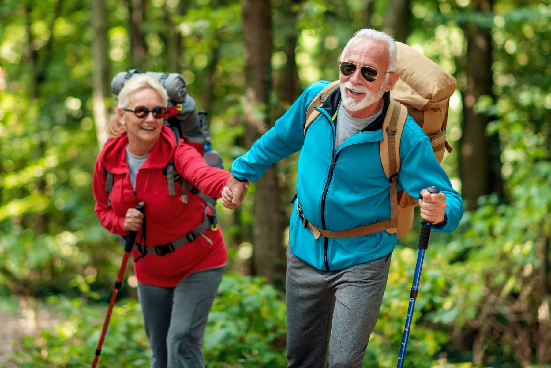 senior couple holding hands while hiking on a trail