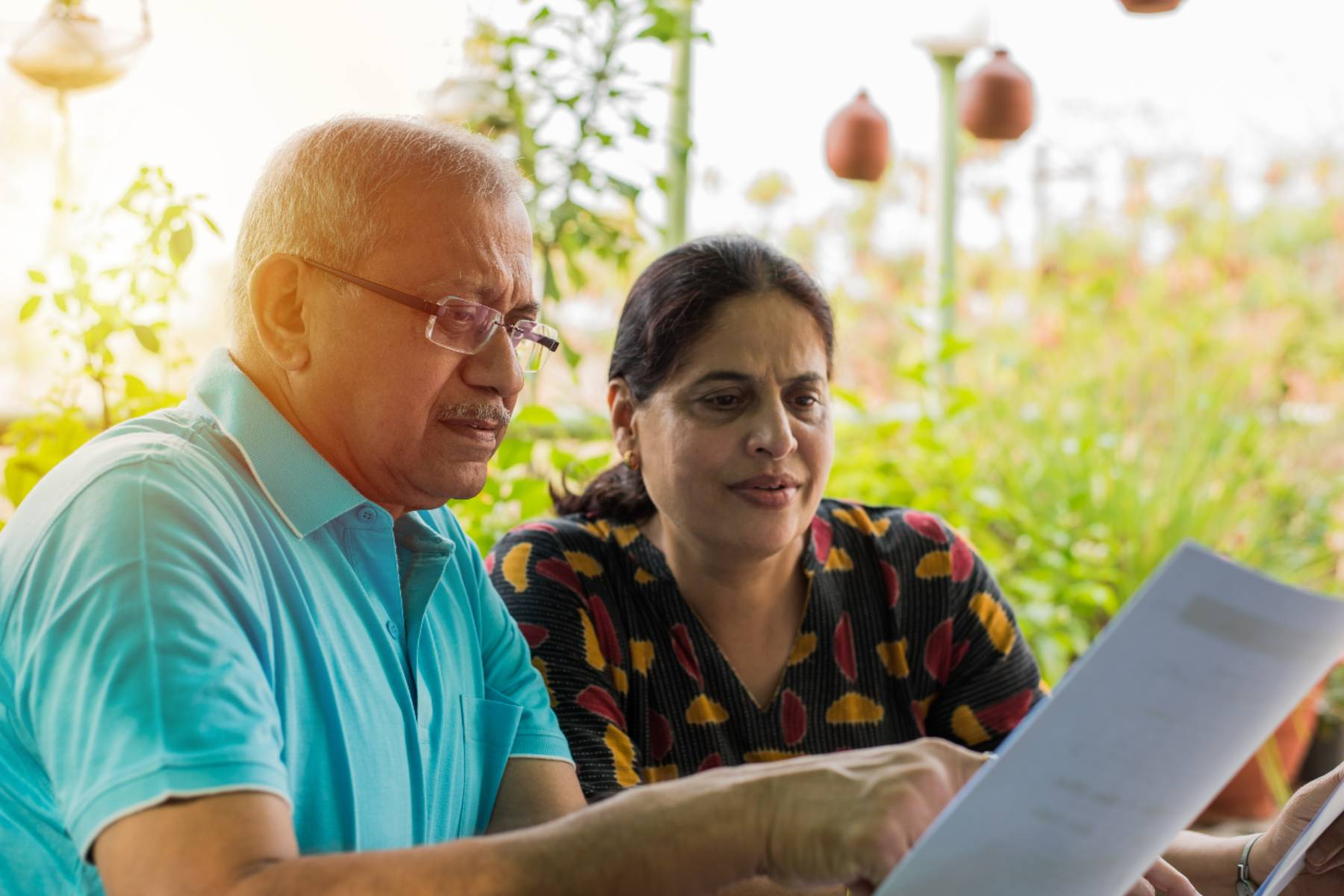 Senior Couple looking over paperwork outdoors
