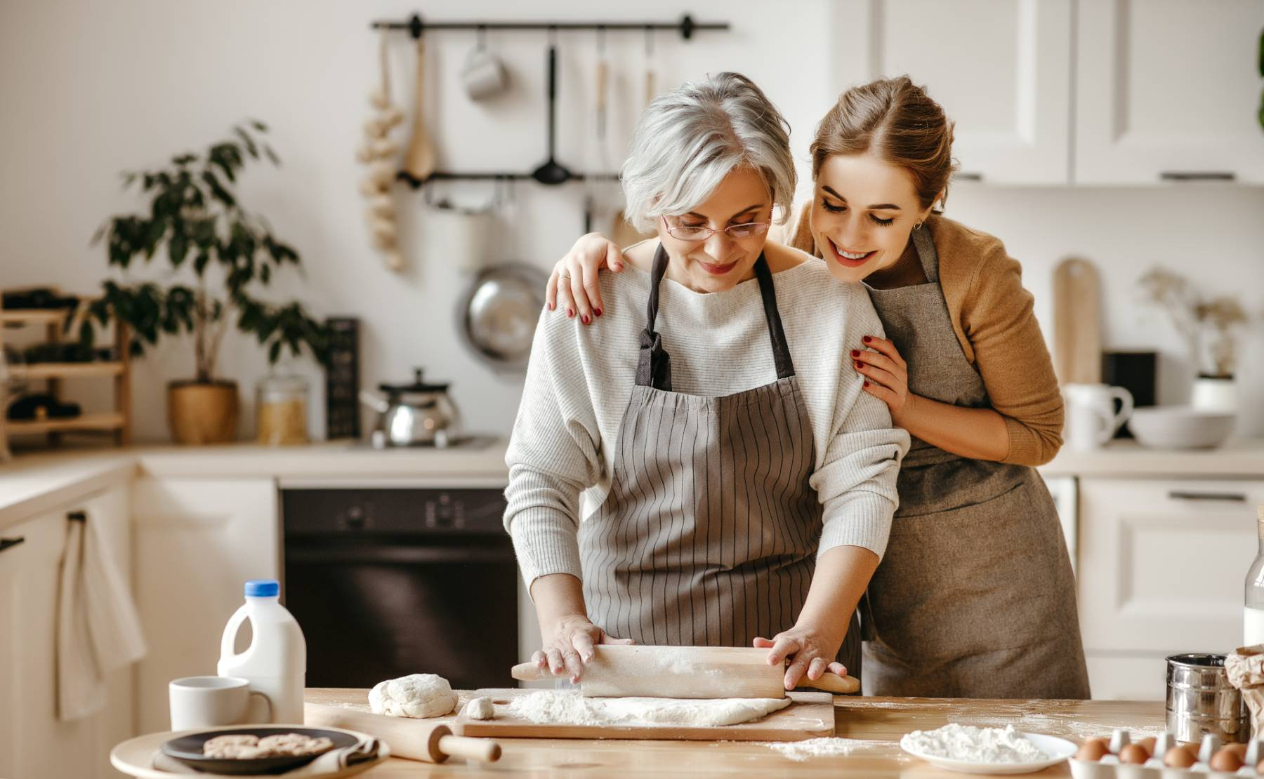 A daughter watches on as her elderly mother uses a rolling pin to roll out dough in the kitchen