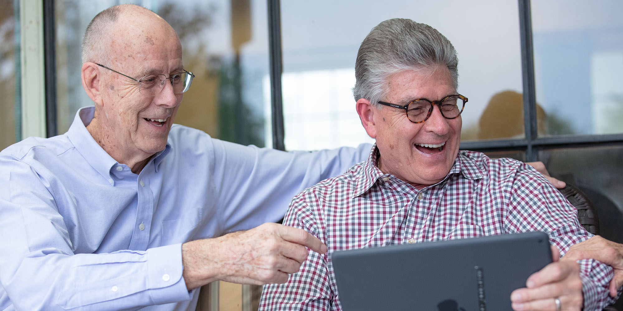 Two senior men looking at a tablet