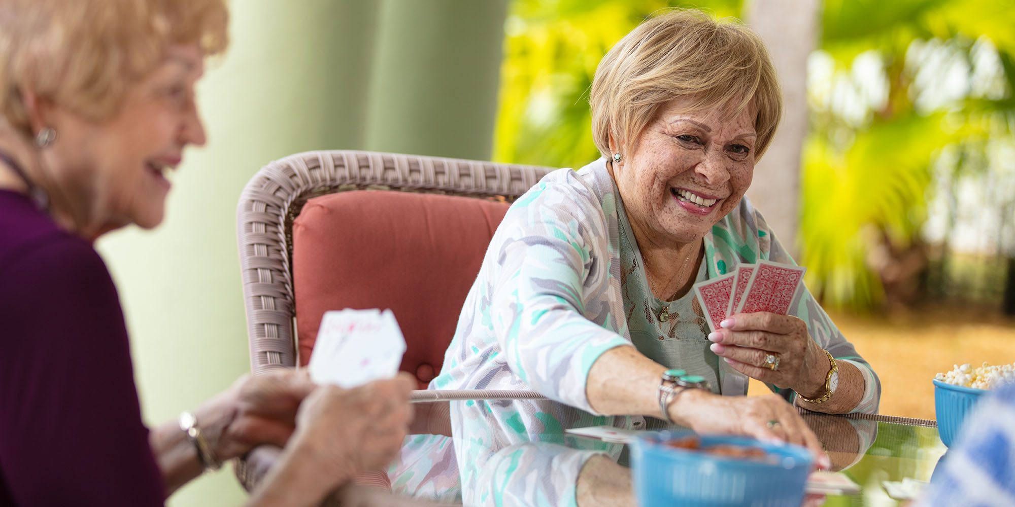 Two senior women playing cards at their Hanceville AL assisted living facility