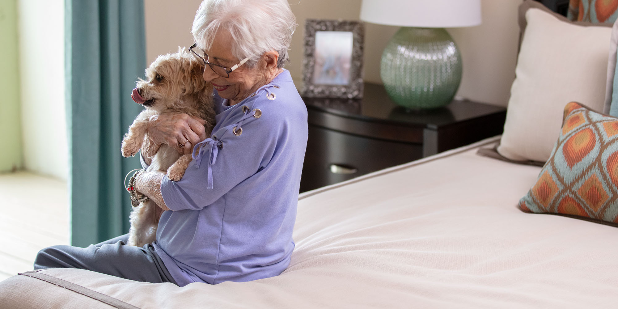 An elderly woman hugging her dog at her San Antonio senior living community