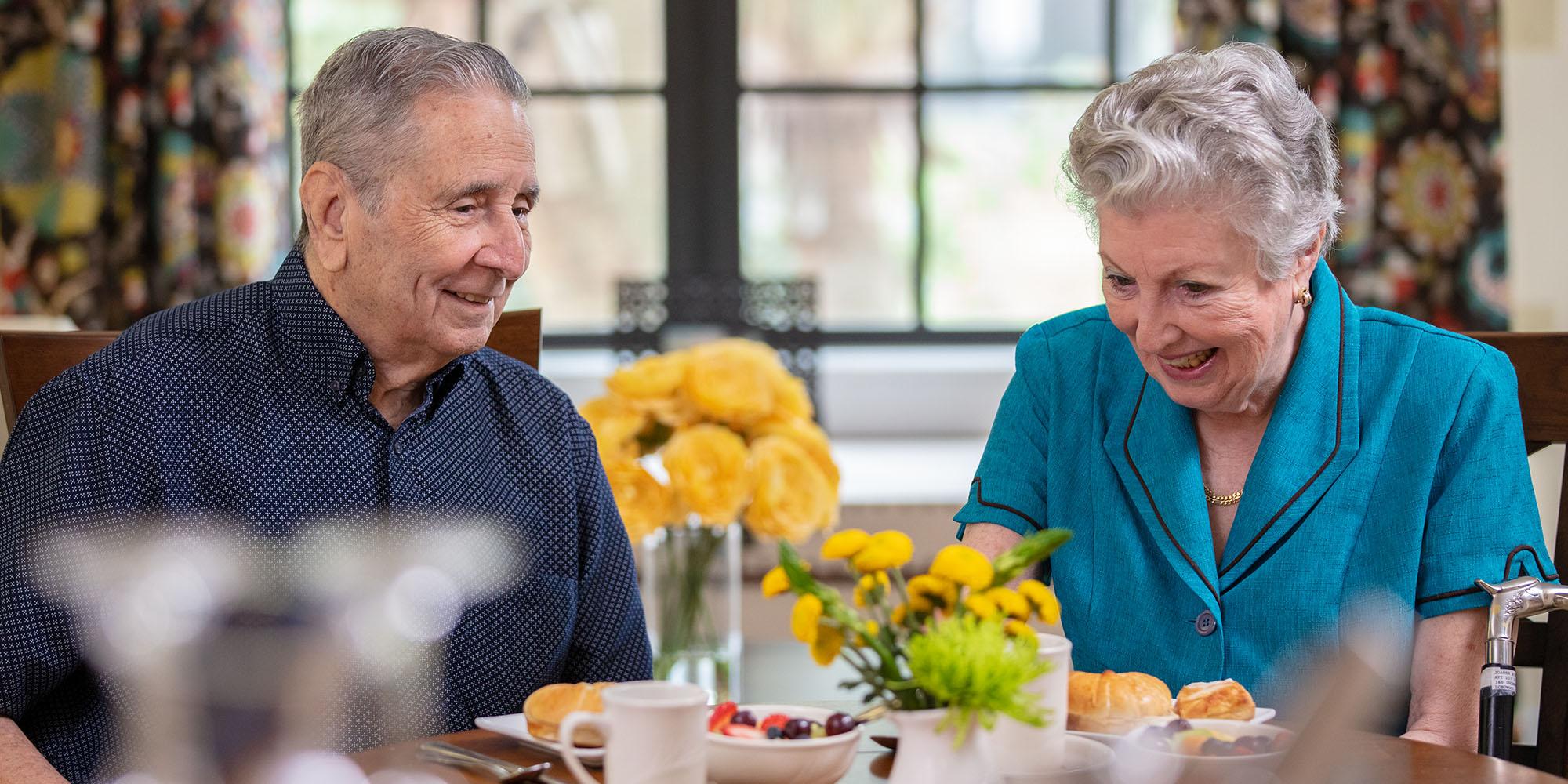 An elderly couple enjoying a meal at their San Antonio senior living community