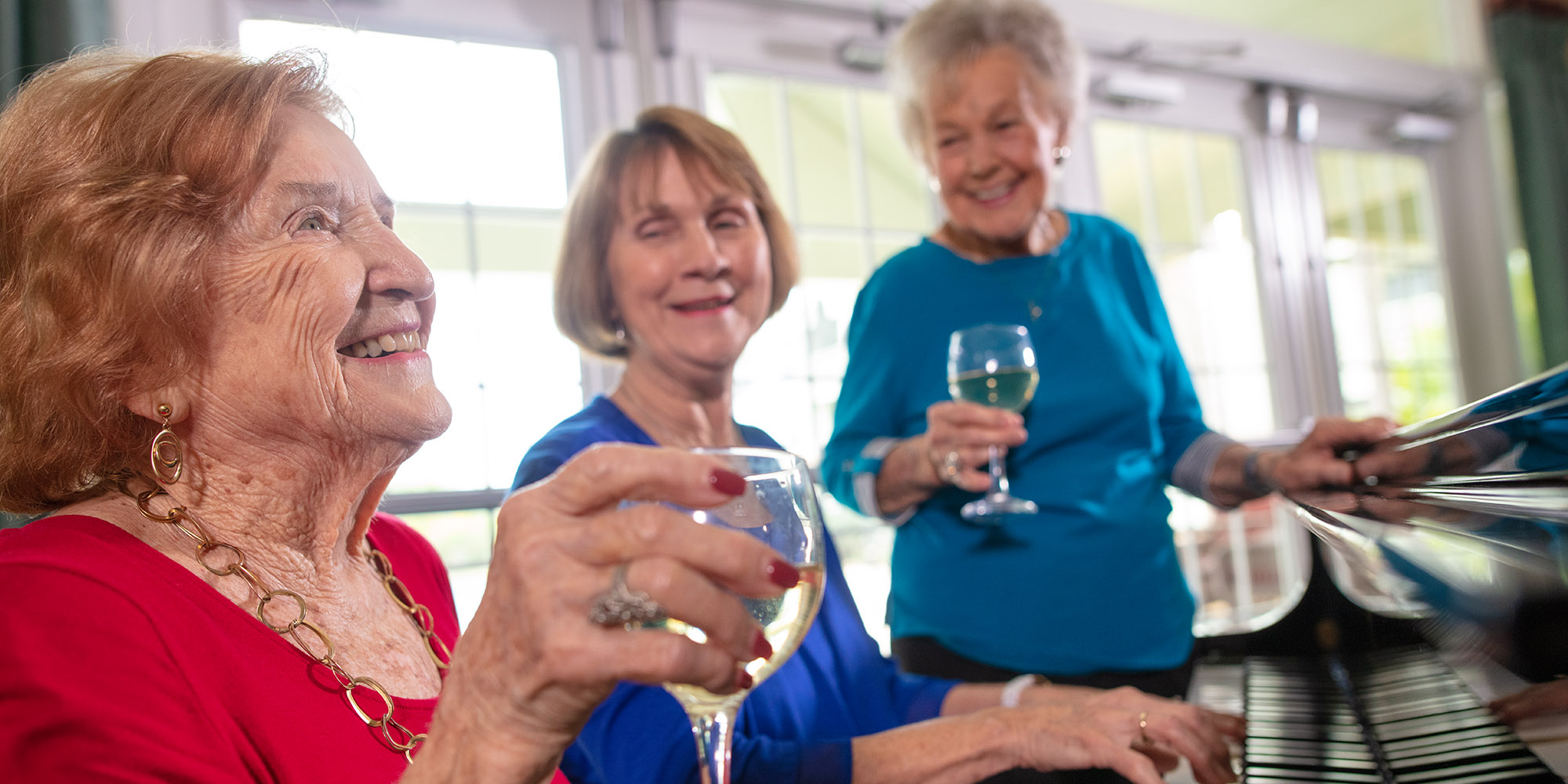 Three senior woman drinking wine and listening to the piano at their Leesburg FL retirement community