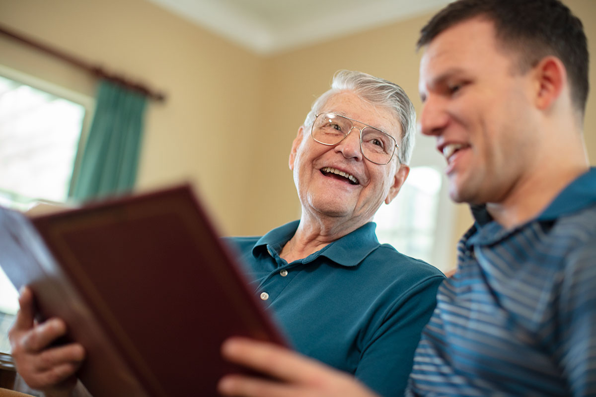 Elderly man looking at a book with his adult son