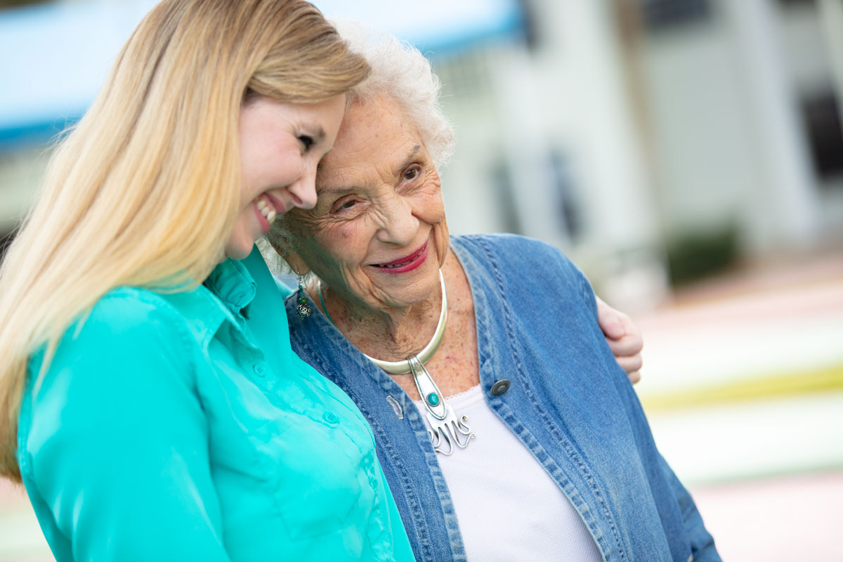 An elderly woman and her daughter stand side by side and smile