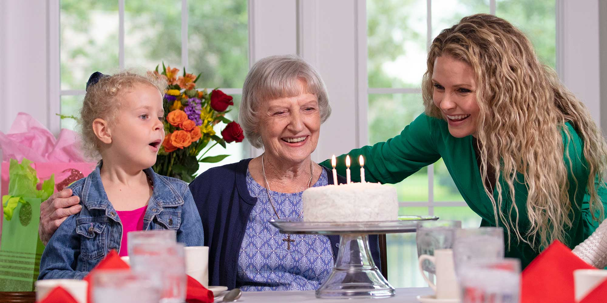 Senior woman celebrating her birthday with her daughter and granddaughter