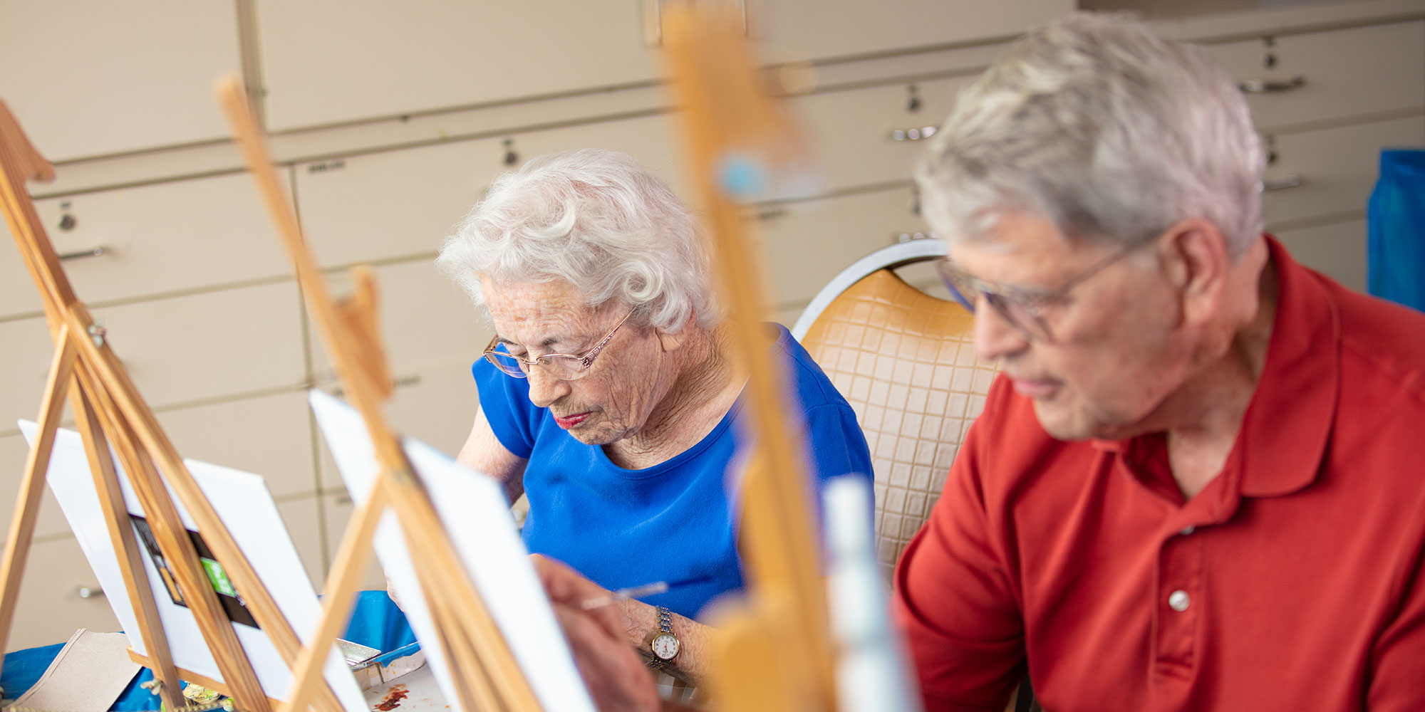 An elderly couple taking a painting class at their Ravenna OH senior living community