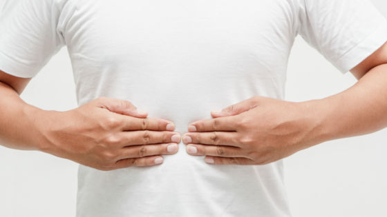 Young man clutching stomach and experiencing acid reflux