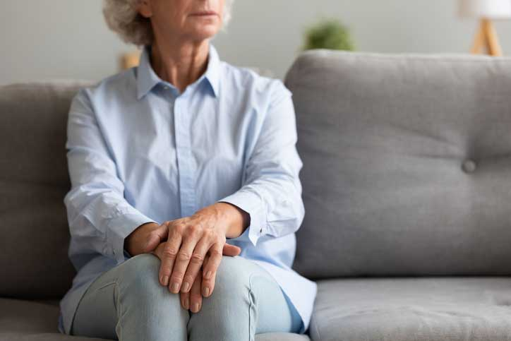 a senior woman sitting with her arms folded over her legs