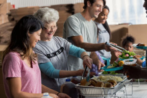 a senior woman volunteering at a soup kitchen